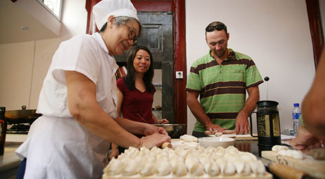 Team USA Olympic rower Bryan Volpenhein, who won a bronze medal in the men's eight rowing event, receives a lesson in making dumplings from master chef Guizhen Wang, left, and cookbook author and chef Jen Lin-Liu Wednesday.