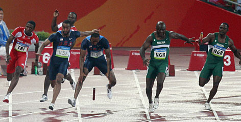 The USA's Darvis Patton, center, and Tyson Gay, second left, drop the baton Thursday during the last 4x100 relay exchange in the qualifying heats. As a result, the Americans are out of the finals.