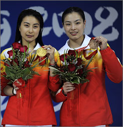 China's Guo Jingjing, right, and Wu Minxia hold up their medals during the women's springboard diving medal ceremony. Jingjing, who has won two diving golds, and other female athletes are a big reason China is leading the gold medal count by 17.