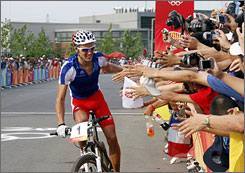 France's Julien Absalon celebrates his win in the Olympic mountain bike race with fans after crossing the finish line on Saturday in Beijing.