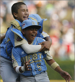 Hawaii's Iolana Akau, left, hugs teammate Christian Donahue after they rallied with six runs in the final inning to defeat Louisiana 7-5 and reach the Little League World Series championship game.