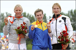 Ukraine's Inna Osypenko-Radomska, center, Italy's Josefa Idem, left, and Germany's Katrin Wagner-Augustin hold up their medals in the kayak single women's final. Osypenko-Radomska beat Idem in a tight finish for the gold.