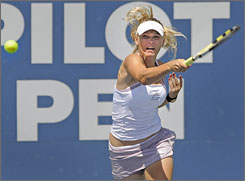 Caroline Wozniacki, of Denmark, hits a forehand during her women's final match with Russia's Anna Chakvetadze, the No. 1 seed, at the Pilot Pen tennis tournament in New Haven, Conn. Wozniacki won the match and her second title this month.