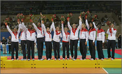 The United States volleyball team waves to the crowd after receiving the silver medal in the women's gold medal match at Capital Stadium in Beijing.