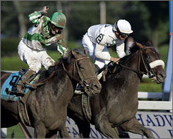 Colonel John with jockey Garrett Gomez aboard, right, holds off Mambo in Seattle with Robby Albarado aboard, to win Saturday's Travers Stakes horse race at Saratoga Race Course in Saratoga Springs, N.Y.