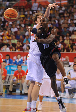 Team USA's Kobe Bryant hangs in the air as he passes around Spain's Pau Gasol in the gold-medal game in Beijing on Sunday. Behind Bryant's 20 points, the U.S. prevailed 118-107.