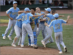 Members of the team from Waipahu, Hawaii, storm the field after winning the Little League World Series championship game with a 12-3 defeat of Matamoros, Mexico. it was the fourth straight year that a U.S. team has won the title.