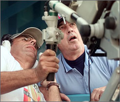In what was probably the first unofficial use of replay in 1999, umpire Frank Pulli examines a TV cameraman's monitor to see whether or not a hit by the Florida Marlins' Cliff Floyd cleared the fence. It was originally called a home run but Pulli changed it to a double after watching the replay.