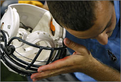 "A Titans staffer checks on the newly installed radio inside a defender's helmet before a preseason game. ""The feedback is almost universally positive,"" league executive vice president of football operations Ray Anderson says of installing the policy. ""The offensive geniuses are going to have to put their thinking caps back on."""