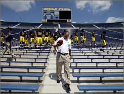 """I don't care that he's an outsider,"" Michigan alum Buddy Moorehouse says of Rich Rodriguez, walking away after taking the team photo at Michigan Stadium on Aug. 17. ""We probably needed an outsider to move the program in the right direction."""