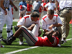 Trainers attend to Ohio State running back Chris Wells after his injury in the third quarter.