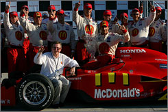 Justin Wilson holds the winner's trophy in the cockpit as team owner Carl Haas (seated) and the rest of this crew join the victory lane celebration at Belle Isle.