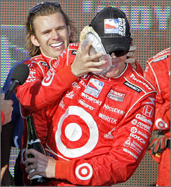 Scott Dixon gets a pie in the face over his shoulder from teammate Dan Wheldon after clinching his second IndyCar championship.