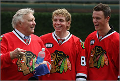 Hockey Hall of Famer Bobby Hull, left, talks with young Chicago Blackhawks' stars Patrick Kane, center, and newly named captain Jonathan Toews at the NHL Winter Classic press conference in July. The young duo represents the future and the present of the Blackhawks.