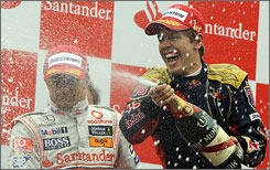 Sebastian Vettel sprays champagne alongside runner-up Heikki Kovalainen after scoring his first Grand Prix win.