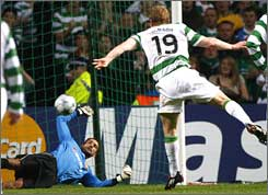 Aalborg goalkeeper Karim Zaza saves a penalty kick by Celtic's Barry Robson.