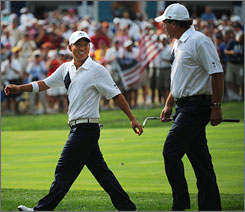 United States teammates Anthony Kim, left, and Phil Mickelson walk to the 15th tee after winning the 14th hole during afternoon four-ball play at the Valhalla Golf Club in Louisville.