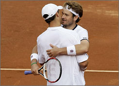 Mardy Fish, right, and Mike Bryan of the U.S. celebrate their wild, five-set victory in Saturday's doubles play.