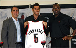 Guard Rudy Fernandez, center, poses with Portland Trail Blazers coach Nate McMillan, right, and general manager Kevin Pritchard during a news conference in Portland, Ore., on Monday. Fernandez won a silver medal with Spain in the Beijing Olympics.