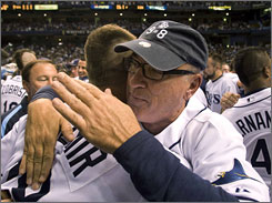 Tampa Bay manager Joe Maddon hugs pitcher Scott Kazmir on Saturday after the Rays clinched their first playoff berth. The 9=8 on Maddon's hat means nine players playing together will end up being one of eight postseason teams.