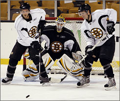 The Bruins' Patrice Bergeron, left, and Phil Kessel, right, prepare to tip the puck on goalie Manny Fernandez during the first full day of their team's training camp in Boston. The Bruins hope Bergeron will stay healthy after missing most of last season with an injury.
