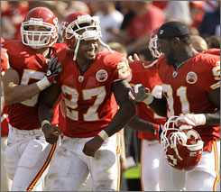 Larry Johnson, center, scored two touchdowns and rushed for 198 yards in the Chiefs' first win of the season on Sunday.