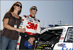 Greg Biffle and his wife, Nicole, stand at attention for the national anthem during pre-race activity at Kansas Speedway.