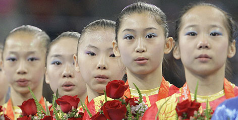 From left, Yang Yilin, Li Shanshan, He Kexin, Jiang Yuyuan and Deng Linlin listen to the Chinese national anthem after the quintet combined to capture the women's team gold medal in gymnastics. International gymnastics officials have verified their ages during the Beijing Games.