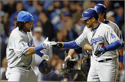 The Los Angeles Dodgers' James Loney, right, celebrates his grand slam home run in the fifth inning which erased a 2-0 deficit to the Chicago Cubs at Wrigley Field. The Dodgers went on to win 7-2 to win Game 1 of the NLDS.