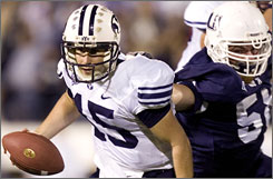 BYU quarterback Max Hall tries to escape from Utah State's Ben Calderwood during the fourth quarter. Hall threw for 303 yards and two touchdowns as the seventh-ranked Cougars extended the nation's longest winning streak to 15 games.