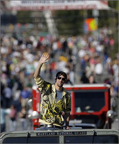 Olympic gold medalist Michael Phelps waves to the crowd during a welcome home parade for him and other Olympic athletes in Towson, Md.