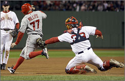 Boston Red Sox catcher Jason Varitek, right, tags out the Los Angeles Angels' Reggie Willits on an attempted suicide squeeze play in the top of the ninth inning. Erick Aybar couldn't get the bunt down, and Willits was caught in a run-down, foiling a potential Angels rally.