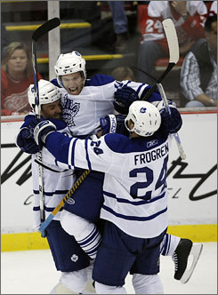 Jonas Frogren, Dominic Moore, center, and Pavel Kubina celebrate Moore's second-period goal as the Maple Leafs spoiled the Red Wings' opener in Detroit.