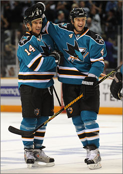 Rob Blake, right, gives Sharks teammate Jonathan Cheechoo a pat on the head after the right winger scored one of his two goals in San Jose's opening win over the Ducks.