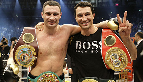 Vitali Klitschko, left, and brother Wladimir pose with their title belts after Vitali claimed the WBC heavyweight title with a technical knockout of Samuel Peter in Berlin. Wladimir holds the IBF and WBO heavyweight belts.
