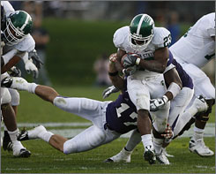 Javon Ringer rushes for some of his 124 yards in Michigan State's 37-20 win on the road at Northwestern. The running back scored twice and now has 1,112 rushing yards on the year.