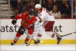 Chicago Blackhawks right wing Martin Havlat, left, carries the puck away from Phoenix Coyotes center    Olli Jokinen. Havlat tied the game with 8:25 left in the second on a highlight-reel goal.