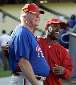 Phillies manager Charlie Manuel, left, and shortstop  Jimmy Rollins share a light moment Monday before Game 4 of the NL Championship Series. Manuel has stayed with the team since the death of his mother, June, last Friday.