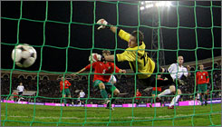 England's Wayne Rooney, second from right, scores past Belarus' goalkeeper Yuri Zhevnov, foreground center, during their World Cup Group Six qualifying soccer match in Minsk, Belarus. England (4-0) is off to its best start in World Cup qualifying and leads Ukraine and Croatia by five points in Group Six going into a six-month break.