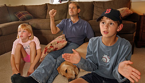 """Red Sox fan Kent Haines, with son Zach and daughter Abby, says it cost $250 for an outing to Fenway Park. """"When you combine the cost of the tickets with the effort it takes to get our fannies in the seats, watching on TV ... sounds pretty good right now,"""" says Haines."""