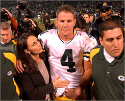 Brett Favre, accompanied by his wife Deanna, exits the field in Oakland after leading the Packers to a win in Oakland one day after the death of his father on Dec. 22, 2003.