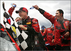 Johnny Benson enjoys a victory shower after his win at Martinsville gave him the points lead.
