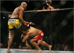 UFC middleweight champion Anderson Silva, left, won at UFC 90 after Patrick Cote, right, suffered a knee injury.