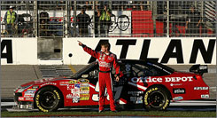 Carl Edwards points to the crowd Sunday after winning the NASCAR Sprint Cup Series Pep Boys Auto 500 at Atlanta Motor Speedway in Hampton, Ga. Edwards sits second in the points standings to defending Sprint Cup champion Jimmie Johnson.