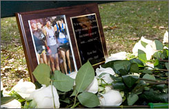 A bunch of roses rest alongside a memorial photo of Ryan Shay in New York City.