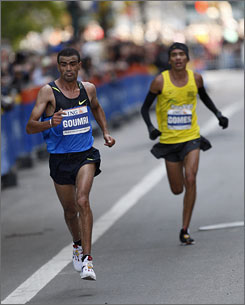 Marilson Gomes dos Santos, in yellow, prepares to pass Abderrahim Goumri late in Sunday's New York City Marathon. Gomes won by 24 seconds.
