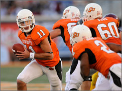 Junior quarterback Zac Robinson, left, makes big plays with his arm and his feet for No. 8 Oklahoma State.