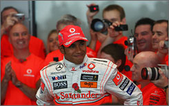 McLaren employees laud Lewis Hamilton for his first  F1 title at the team's headquarters in Woking, England.
