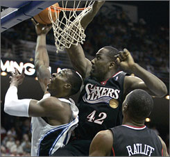 Orlando Magic center Dwight Howard, left, goes in for a basket while Philadelphia 76ers forward Elton Brand, center, and Theo Ratliff try to defend during the second half of their game in Orlando. Howard had 14 points and eight rebounds, and the Magic won 98-88.