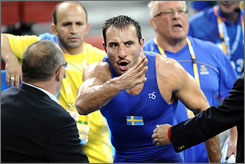 Ara Abrahamian argues with officials after his Greco-Roman semifinal match was halted Aug. 14 in Beijing.